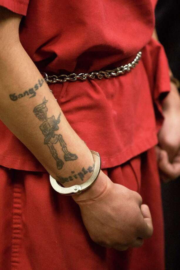 "Andrew Patterson wears handcuffs and a ""Gangsta Disciples"" tattoo on his forearm duringhis sentencing Friday for the murder of Justin Ferrari. Photo: JORDAN STEAD, SEATTLEPI.COM / SEATTLEPI.COM"