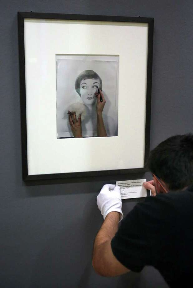An employee adjusts a label under a photo by German-born American photographer Erwin Blumenfeld during the preparation of an exhibition at the Jeu de Paume museum in Paris. Photo: Remy De La Mauviniere, STF / AP
