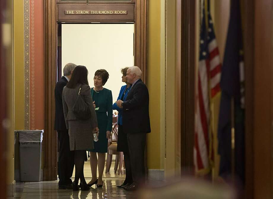 Sen. Susan Collins, R-Maine (center) discusses budget negotiations with Senate colleagues on Capitol Hill. Photo: Evan Vucci, Associated Press