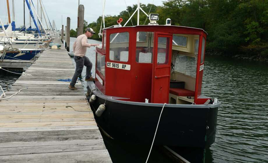 Chris German, of Connecticut Community Boating, checks on the non-profit's boats Friday, Oct. 11, 2013.  The vessels were taken by Bridgeport's Harbor Master and moved to Captain's Cove Marina. Photo: Autumn Driscoll / Connecticut Post