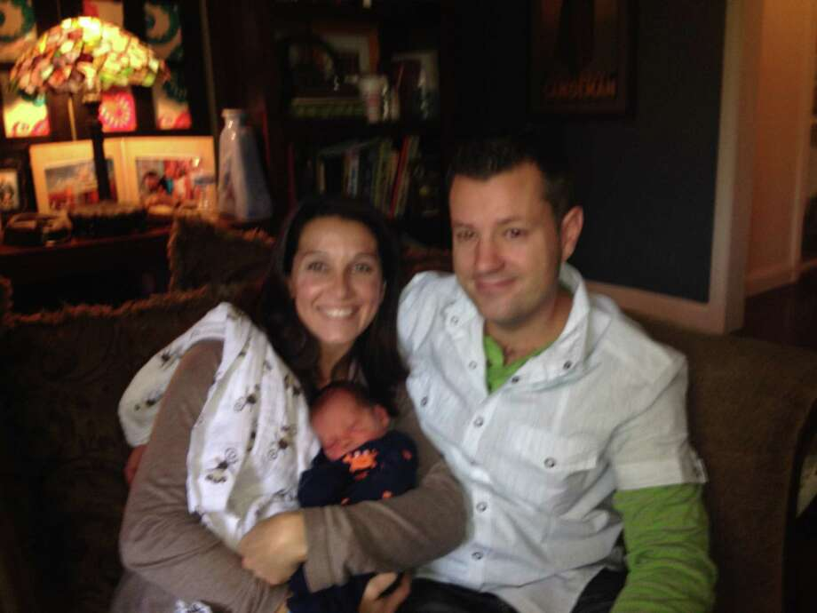 Julie and Jeremiah TenEyck, sit with their newborn son, Blake, at their home in Ballston Spa Friday, Oct. 11, 2013. Blake was born in the family minivan early Wednesday morning as Jeremiah TenEyck drove his wife toward Glens Falls Hospital.