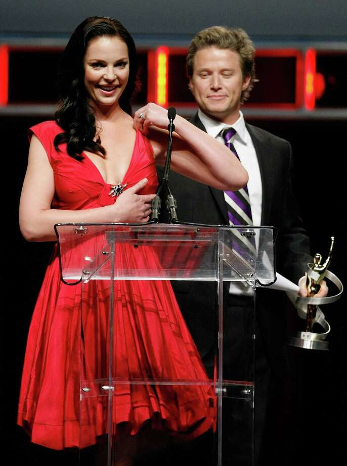 Showest awards host Billy Bush holds up Katherine Heigl's dress after it broke while she was accepting an acting award. Photo: Ethan Miller, Getty Images / 2010 Getty Images