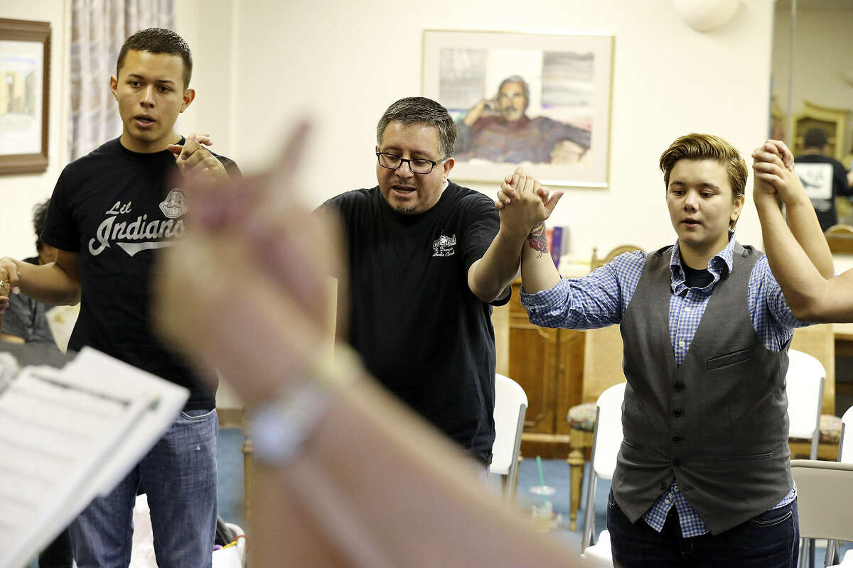 Michael Torres, (from left), Laurence Gonzalez and Meagan Mireles pray during a Dignity San Antonio service. The sessions resemble Masses as much as possible, so there were prayers for the sick, the jobless, the pope and archbishop.
