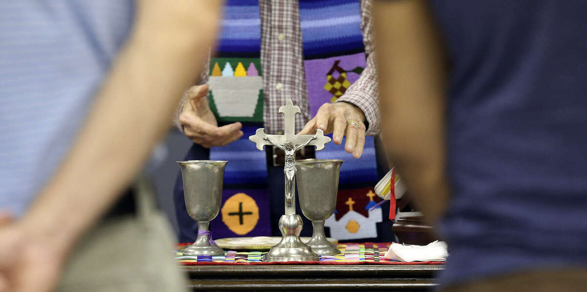 A table holding a crucifix and candles serves as the altar during the Dignity service.