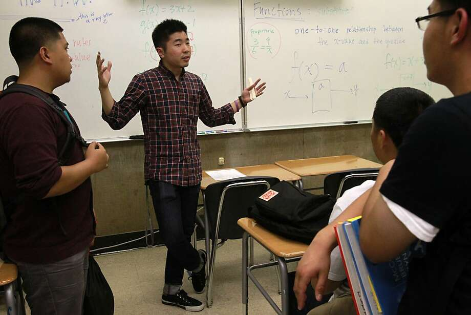 Richmond High math teacher Andrew Kim, 23, gives details about the new free, SAT math prep class held after school weekly - the students are Joey Lumagbas (left), Joey Saephan and Raul Vicuna III, all 17. Photo: Leah Millis, The Chronicle