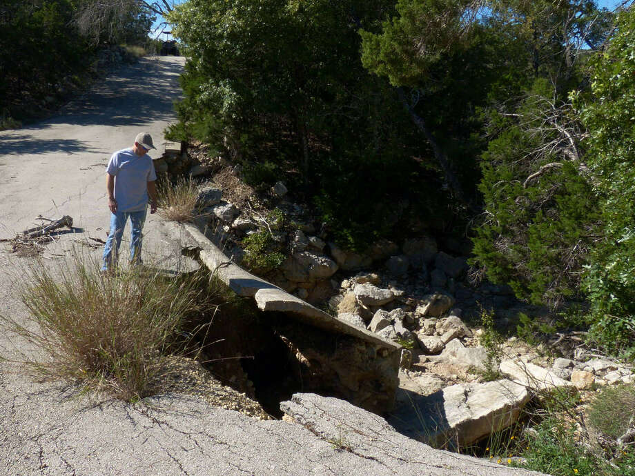 Carl Dominguez examines a portion of a road built over a creek in the Clearwater Ranch subdivision. Sitting moribund after Bexar County prohibited development around 2007, the subdivision has gotten a new lease on life. Photo: Photos By Billy Calzada / San Antonio Express-News