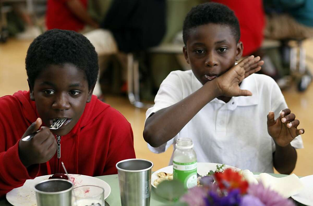 Amaai McCoy, left and Ezra Mckinley eat their quinoa macaroni and cheese prepared by Justin Everett, chef of Cavallo Point Resort, and the chefs from the Conscious Kitchen project at the Martin Luther King Academy, Wednesday September 11, 2013, in Marin City, Calif. The Conscious Kitchen project is chefs from across the Bay Area working with the schools to create healthier meals for the low-income communities.