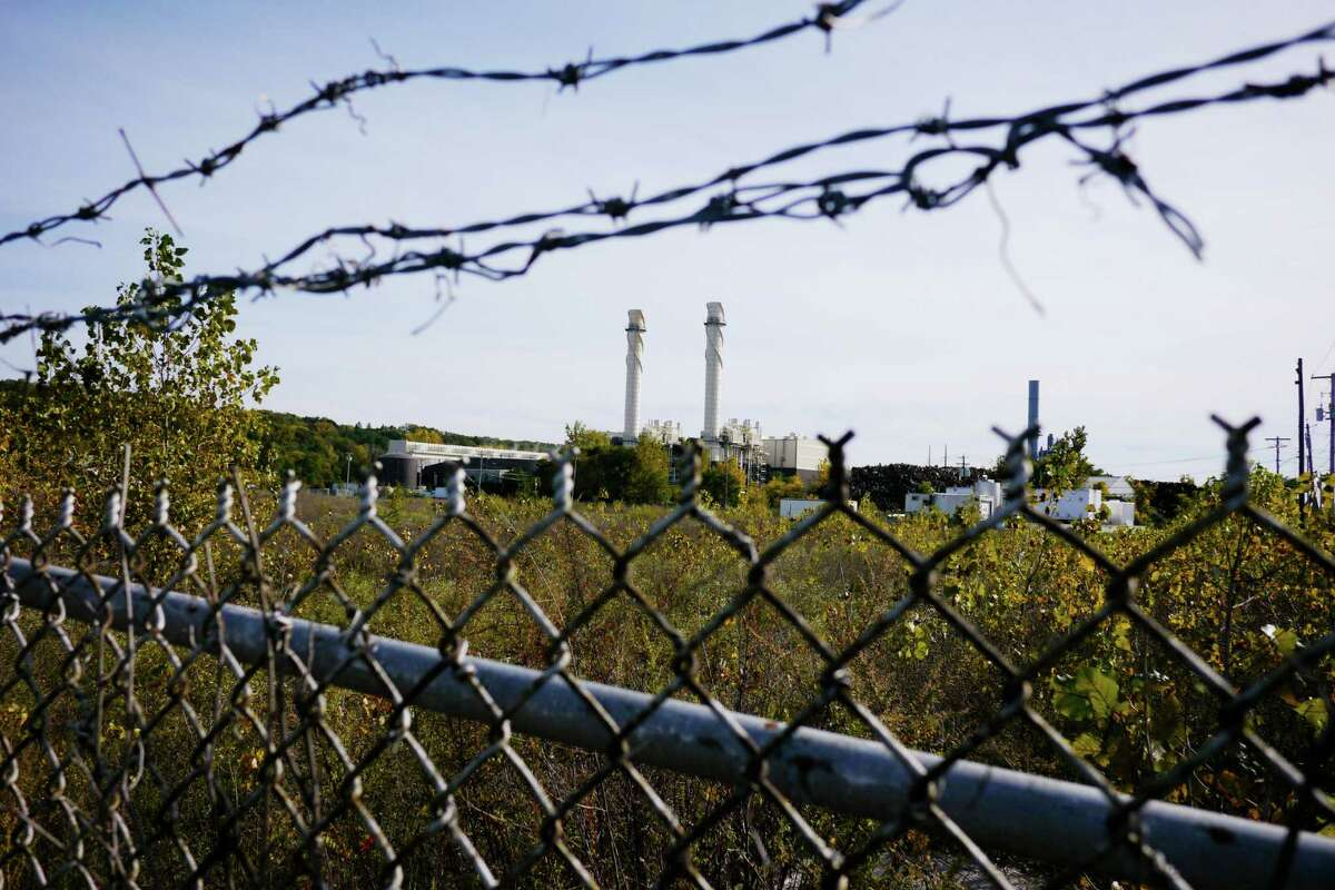 The stacks of the Empire Generating power plant are seen in the background on Wednesday, Oct. 9, 2013, in Rensselaer, NY. In the foreground a chain link fence surrounds the industrial property where a BASF plant once stood. (Paul Buckowski / Times Union)