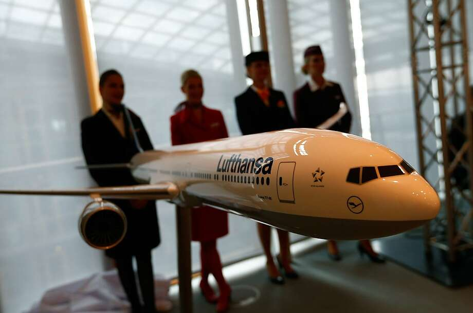 Flight crew members for the German airline Lufthansa stand behind a model of a Boeing 777-9X jet at a news conference in Frankfurt, Germany. Boeing has an $11 billion order from Lufthansa for 34 of the jets. Photo: Ralph Orlowski, Bloomberg