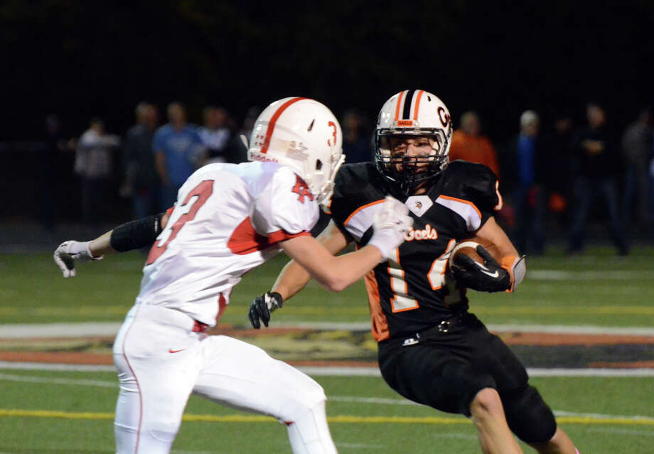 Shelton's Michael Pingree (14) carries the ball as Fairfield Prep's John Snopkowski (3) defends during the football game at Shelton High School on Friday, Oct. 11, 2013. Photo: Amy Mortensen / Connecticut Post Freelance