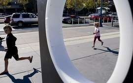 Eli, 8, and Scarlett Pearson, 5, of Oakland are seen running past the Exploratorium sign at The Embarcadero in San Francisco, Calif. on Friday, Oct. 11, 2013.