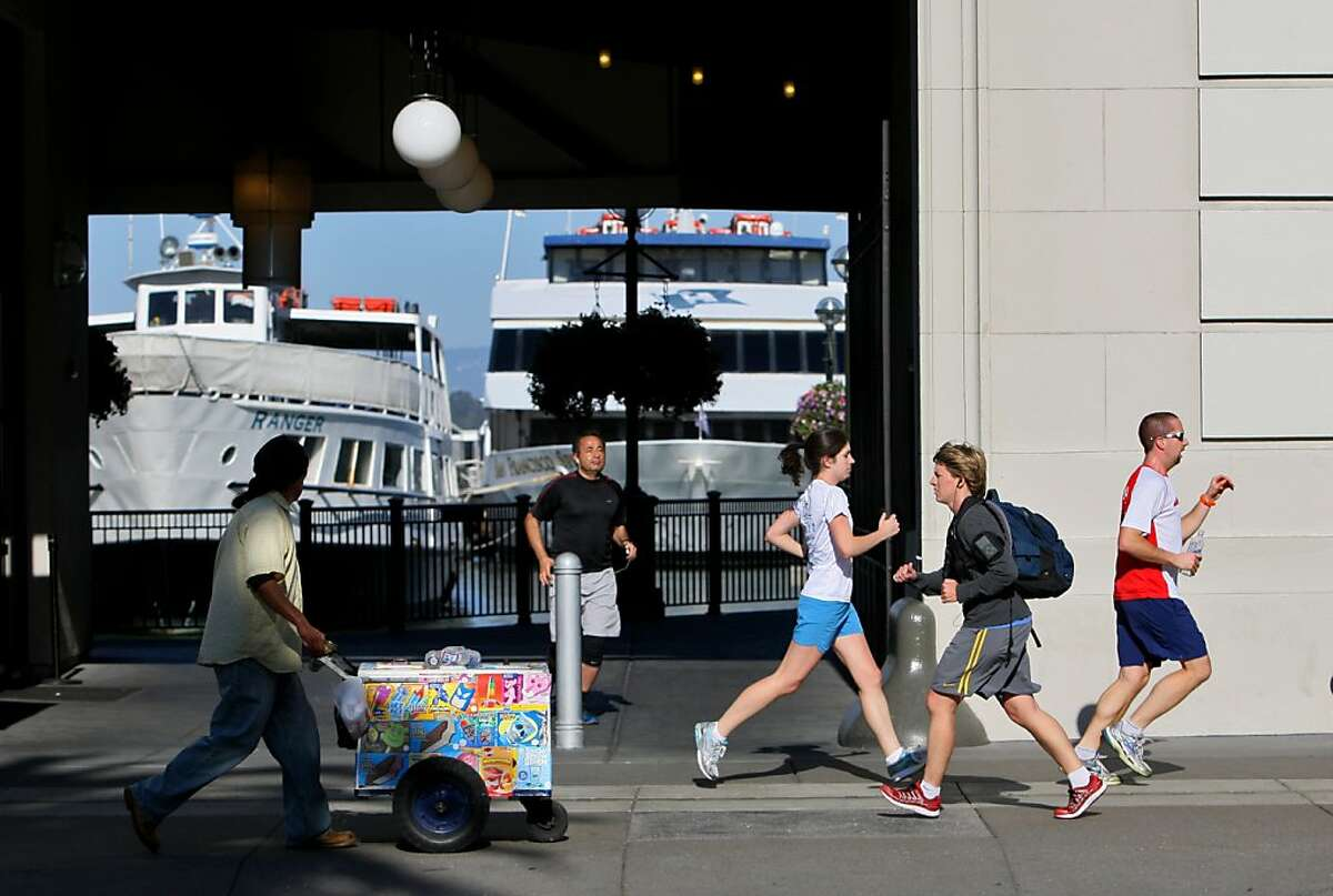 Runners and an ice cream vendor are seen passing Pier 3 ot The Embarcadero in San Francisco, Calif. on Friday, Oct. 11, 2013.
