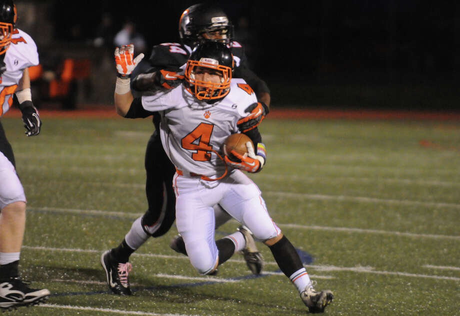 Stamford's Tyquan Bonaparte puts a stop to Ridgefield's Jack Boscia as Stamford High School hosts Ridgefield in a football game in Stamford, Conn., Oct. 11, 2013. Photo: Keelin Daly / Stamford Advocate Freelance