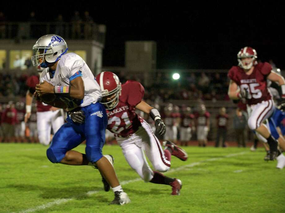 Bunnell's Zhyaire Fernandes, 25, tries to turn the corner as Bethel's Matthew Sanjiacomo, 21, catches him during a boys High School football game between Bunnell High School and Bethel High School in Bethel, Conn, on Friday, October 11, 2013. Photo: H John Voorhees III / The News-Times Freelance
