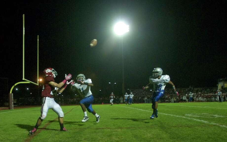 Bethel's James Giannone, 20, waits for a touchdown pass while Bunnell's Justin Townsend, 11, and Brett Bogdwicz, 30 , try to reach him during a boys High School football game between Bunnell High School and Bethel High School in Bethel, Conn, on Friday, October 11, 2013. Photo: H John Voorhees III / The News-Times Freelance