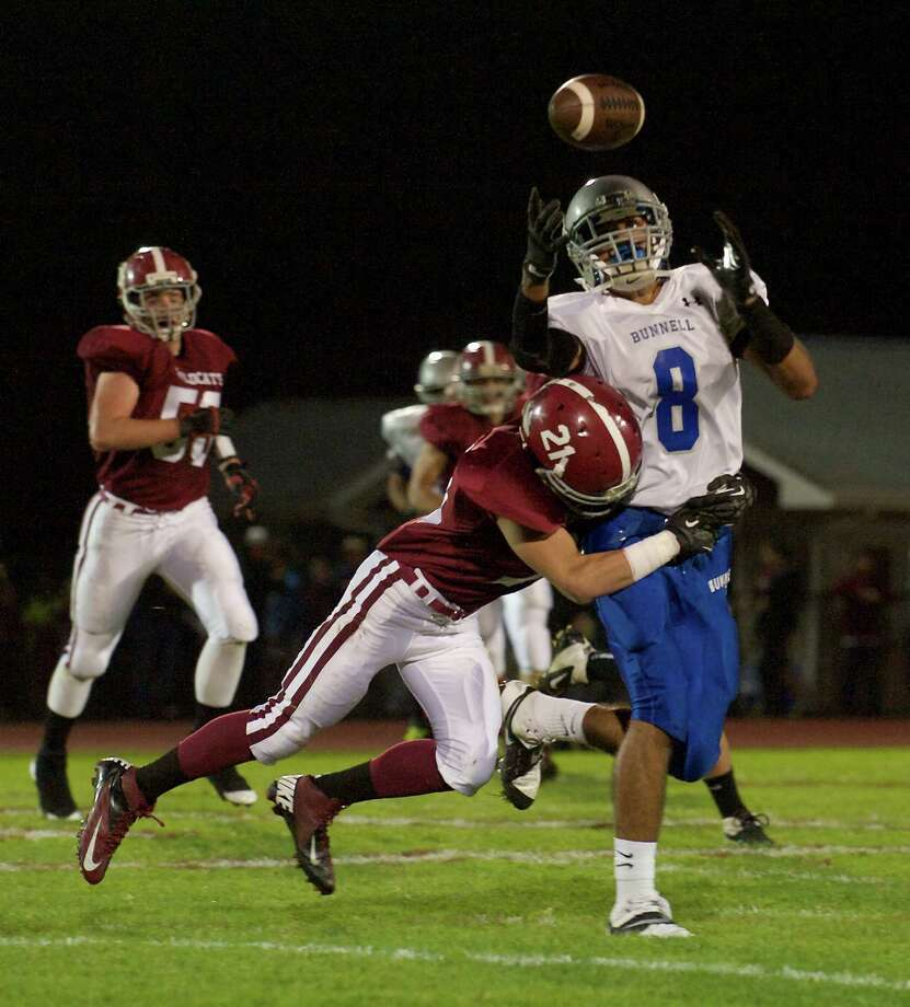 Bunnell's Tegh Terrell, 8, tries to hang on to a pass as he is hit by Bethel's Matthew Sanjiacomo, 21 during a boys High School football game between Bunnell High School and Bethel High School in Bethel, Conn, on Friday, October 11, 2013. Photo: H John Voorhees III / The News-Times Freelance