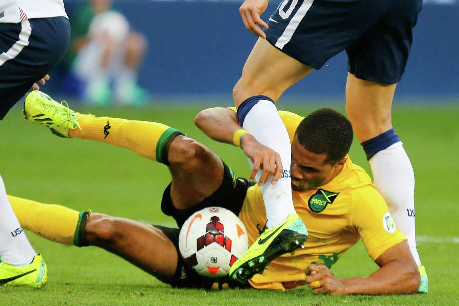 KANSAS CITY, KS - OCTOBER 11:  Ryan Johnson of Jamaica slides under Geoff Cameron #20 of the U.S. Men's National Soccer Team while attempting to regain possession inside the USA penalty box Sporting Park late in the first half on October 11, 2013 in Kansas City, Kansas. Photo: Kyle Rivas, Getty Images / 2013 Getty Images