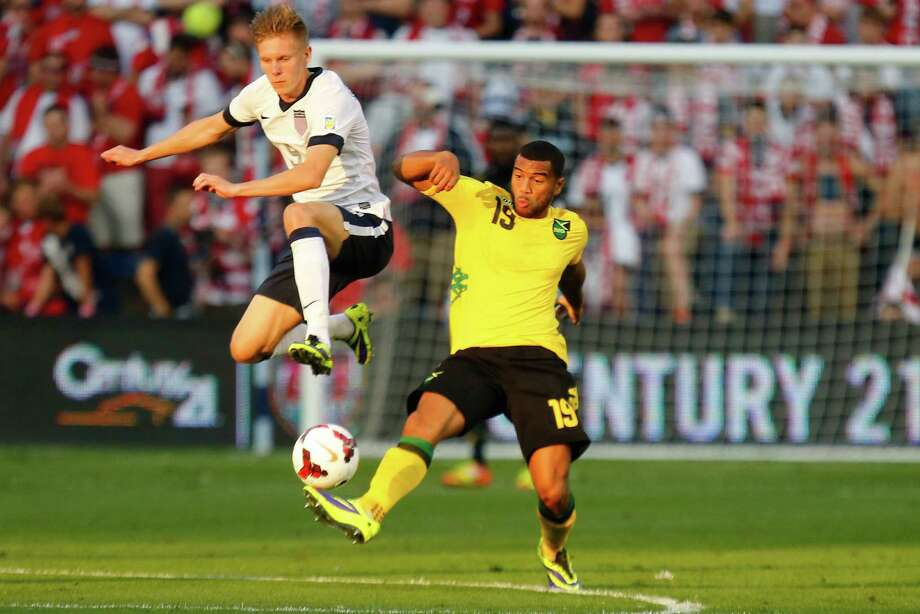KANSAS CITY, KS - OCTOBER 11:  Aron Johannsson #9 of the U.S. Men's National Soccer Team tips the ball away from Adrain Mariappa #19 of Jamaica at midfield in the first half against the / at Sporting Park on October 11, 2013 in Kansas City, Kansas. Photo: Kyle Rivas, Getty Images / 2013 Getty Images