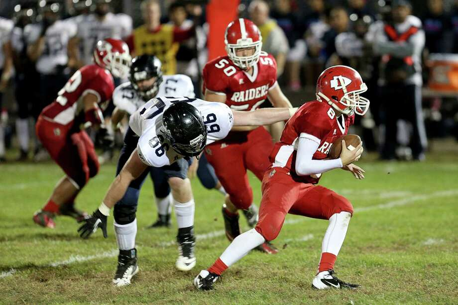 Mike Ross Connecticut Post freelance - Ansonia High School's #66 Timothy Schmidheini gives defensive pressure to Derby High School's quarterback # Michael Kreiger during Friday evening match-up. Ansonia would remain un-defeated and winning the game 62-28. Photo: Mike Ross / Mike Ross Connecticut Post freelance - @www.mikerossphoto.com