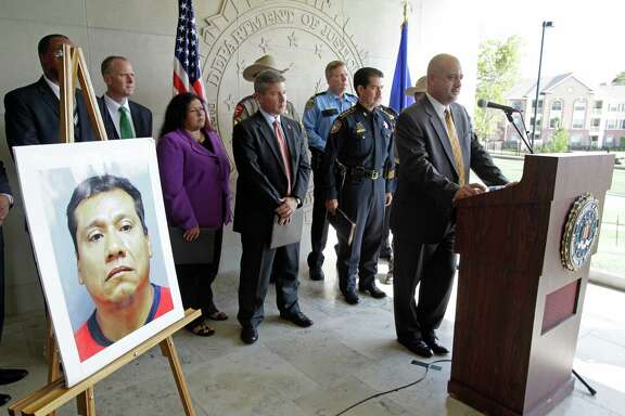 "A photo of Alfonso ""Poncho"" Diaz-Juarez is displayed as Special Agent in Charge Stephen Morris speaks Friday at the FBI's Houston headquarters. A task force is seeking the public's help in apprehending Diaz-Juarez on human trafficking charges."