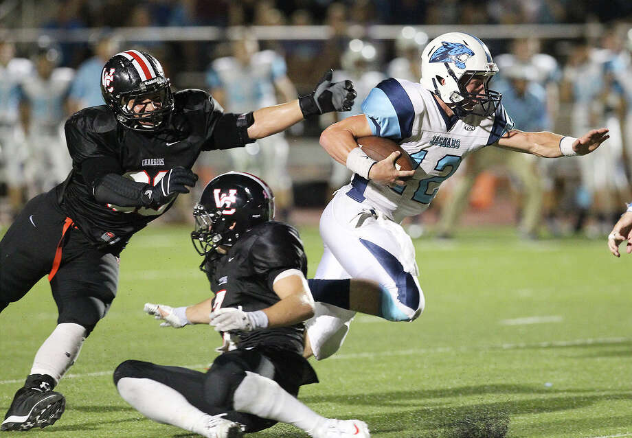 Johnson Jaguars quarterback Hunter Rittimann (12) slips a tackle from Churchill Chargers' Jonah Kucinski-Stewart (90) as he heads for a touchdown at Heroes Stadium on Friday, Oct. 11, 2013. Photo: Kin Man Hui, San Antonio Express-News / ©2013 San Antonio Express-News