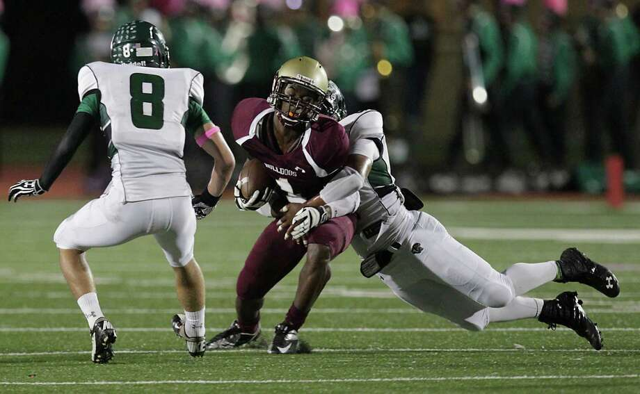 Summer Creek's Avral Jeffery center, is tackled by Kingwood's Jared Como during the second quarter of high school football game action at Humble ISD's Turner Field Friday, Oct. 11, 2013, in Humble. Photo: James Nielsen, Houston Chronicle / © 2013  Houston Chronicle