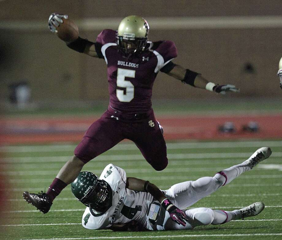 Summer Creek's Byron Frances top, jumps over Kingwood's Jared Como during the second quarter of high school football game action at Humble ISD's Turner Field Friday, Oct. 11, 2013, in Humble. Photo: James Nielsen, Houston Chronicle / © 2013  Houston Chronicle