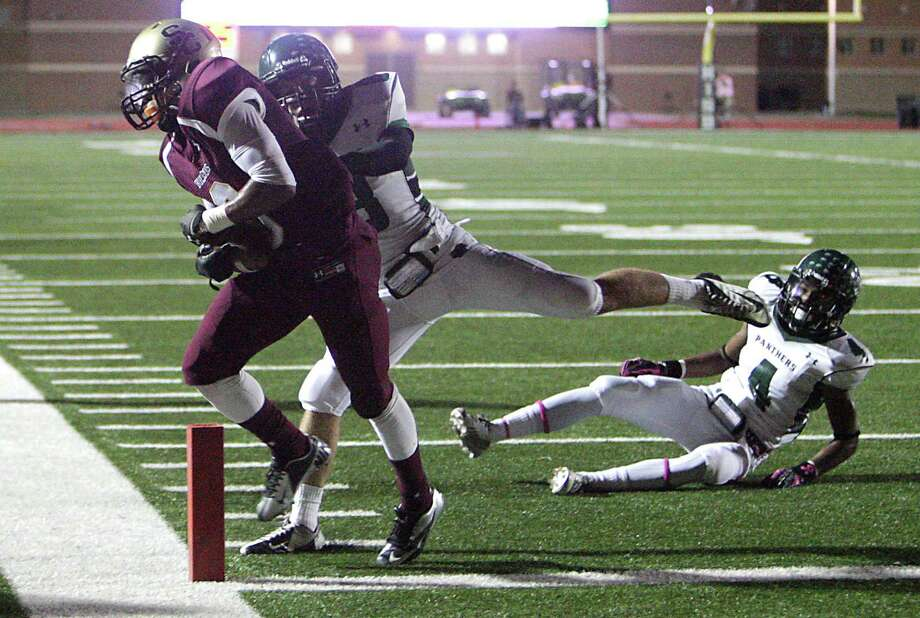 Summer Creek's Torrey Johnson left, pulls in a pass over Kingwood Caleb Lewallen to score a touchdown during the second quarter of high school football game action at Humble ISD's Turner Field Friday, Oct. 11, 2013, in Humble. Photo: James Nielsen, Houston Chronicle / © 2013  Houston Chronicle