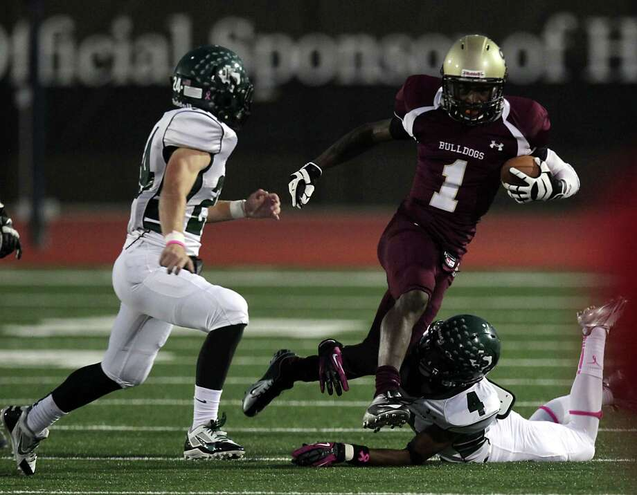 Summer Creek's Arval Jeffrey center, is tackled by Kingwood's Garrett Velko left, and Jared Como right, during the first quarter of high school football game action at Humble ISD's Turner Field Friday, Oct. 11, 2013, in Humble. Photo: James Nielsen, Houston Chronicle / © 2013  Houston Chronicle
