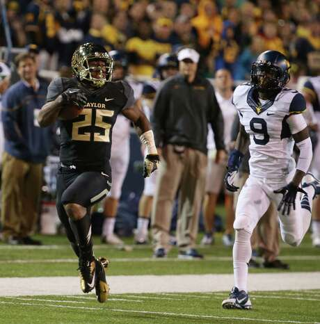 Baylor running back Lache Seastrunk, outrunning West Virginia safety K.J. Dillon last week, is second nationally in rushing yards per game at 147.3. Photo: Rod Aydelotte / Associated Press
