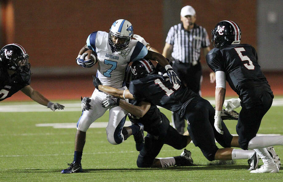 Johnson Jaguars' Darion McElhannon (07) runs for yardage despite tackles by Churchill Chargers defenders at Heroes Stadium on Friday, Oct. 11, 2013. Photo: Kin Man Hui, San Antonio Express-News / ©2013 San Antonio Express-News