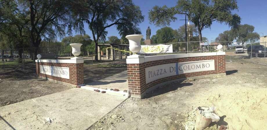 New signs mark the Piazza di Colombo. The Christopher Columbus Italian Society hopes to revive the park and add mixed-use buildings around San Francesco di Paola Catholic Church. Photo: Benjamin Olivo / San Antonio Express-News