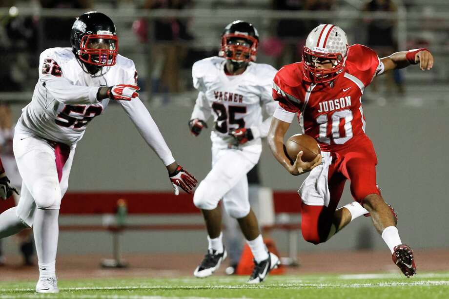 "Judson quarterback Rayjohn Austin-Ramsey (right) scrambles for yardage as Wagner's Charles Harris (left) and Willie Hillman come on to defend during the first half of the ""Hammer Bowl"" at Rutledge Stadium on Friday, Oct. 11, 2013.  MARVIN PFEIFFER/ mpfeiffer@express-news.net Photo: Marvin Pfeiffer, San Antonio Express-News / Express-News 2013"
