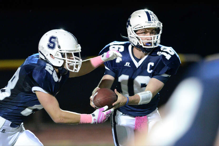 Staples #16 Jack Massie hands off to #28 Jack Greenwald as Staples High School hosts Fairfield Ludlowe High School in varsity football in Westport, CT  on Fri. Oct. 11, 2013. Photo: Shelley Cryan, Stamford Advocate Contributed / Stamford Advocate contributed