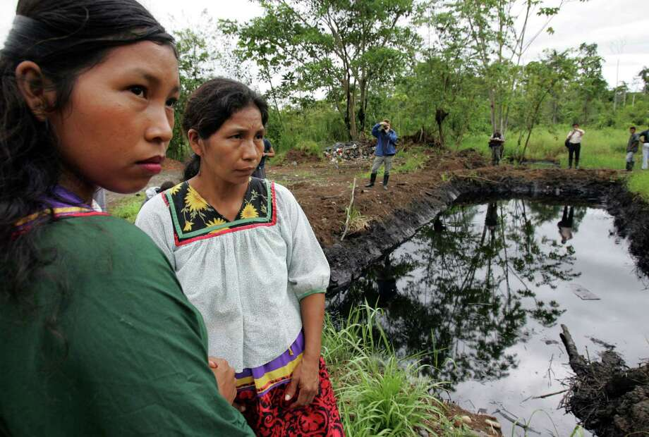 This 2005 photo shows Cofan indigenous women standing near a pool of oil in Ecuador's Amazonian region. A class-action lawsuit against Chevron, led by New York lawyer Steven Donziger, was nearing a billion-dollar settlement, until Chevron argued that Donziger's diary proved he manipulated the legal system. Photo: Dolores Ochoa, STF / AP
