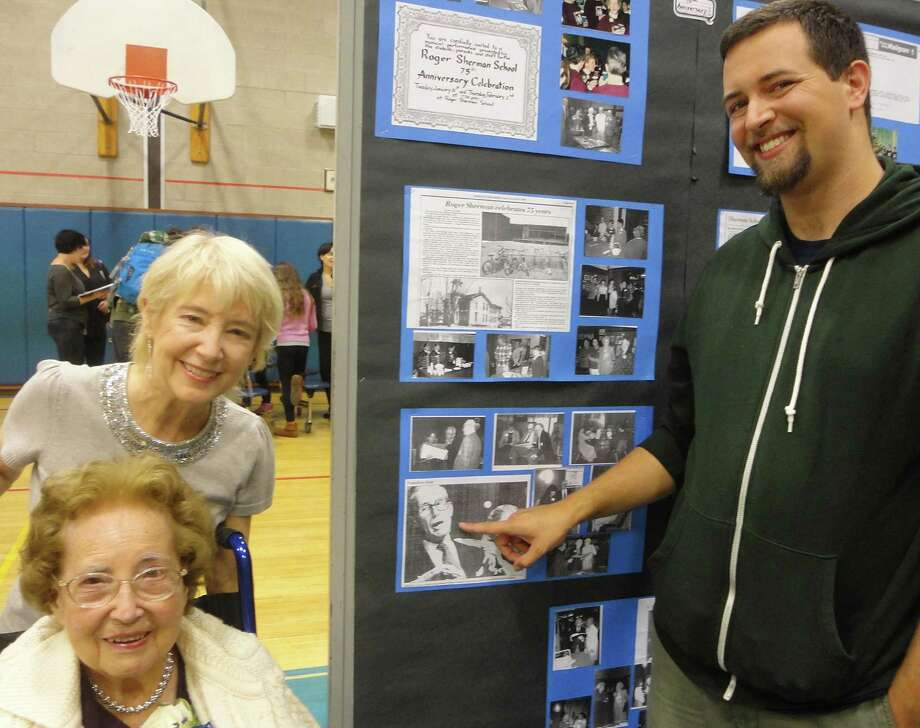 At the 100th anniversary reception at Roger Sherman Elementary School on Friday night, hundreds of alums, former teachers and at least one former principal joined the celebration. Among those attending was the family of Walter Holt, who served as principal from 1963 to 1973. Pictured here, from left to right, are his daughter Sharon Cloutier of Trumbull, widow Ruby Holt of Fairfield and grandson Nicolas Cloutier of Bristol, as they look at a photo of Walter Holt on a display board. FAIRFIELD CITIZEN, CT 10/11/13 Photo: Meg Barone / Fairfield Citizen contributed