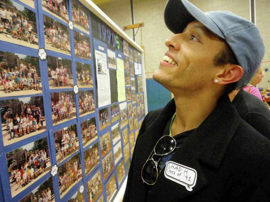 Chad Hunter, who graduated from Roger Sherman School in 1991, looks at a display board of photos in the school gym Friday during the school's 100th anniversary celebration. FAIRFIELD CITIZEN, CT 10/11/13 Photo: Meg Barone / Fairfield Citizen contributed