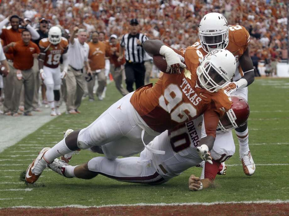 Texas defensive tackle Chris Whaley (96) scores a touchdown after intercepting a pass against Oklahoma quarterback Blake Bell (10) during the first half. Photo: LM Otero, Associated Press