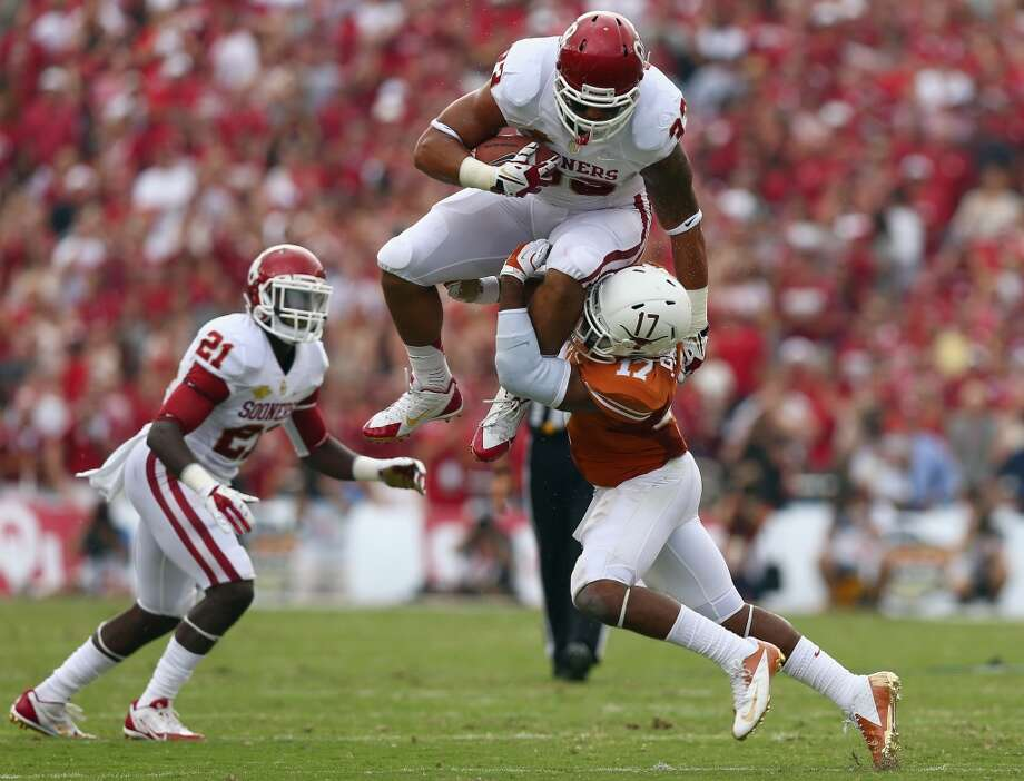 Oklahoma fullback Trey Millard (33) leaps over Texas defender Adrian Phillips (17) during the first half. Photo: Tom Pennington, Getty Images