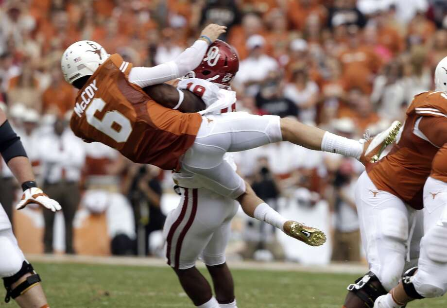 Texas quarterback Case McCoy (6) is knocked off his feet Oklahoma linebacker Eric Striker (19) after releasing a pass during the first half. Photo: LM Otero, Associated Press