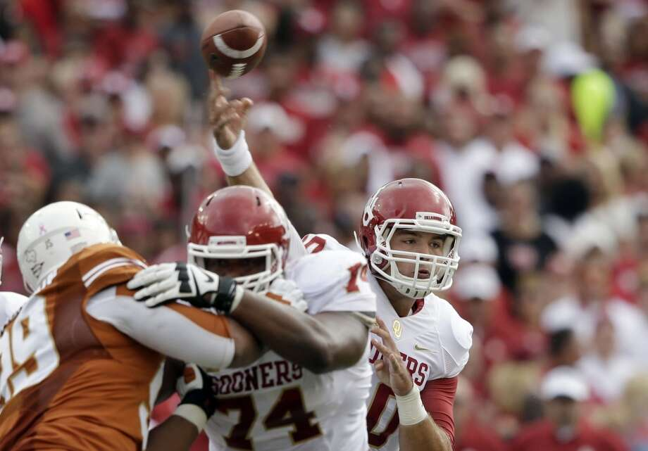 Oklahoma quarterback Blake Bell (10) passes as offensive linesman Adam Shead (74) blocks Texas defensive tackle Desmond Jackson (99) during the first half. Photo: LM Otero, Associated Press