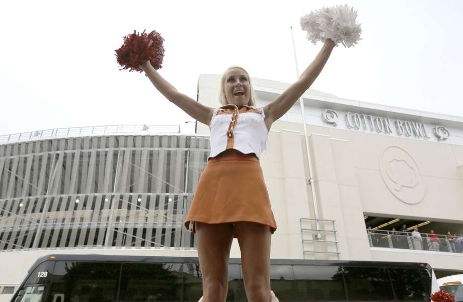 A Texas cheerleader yells as she is hoisted up while her team arrives on Saturday morning. Photo: LM Otero, Associated Press