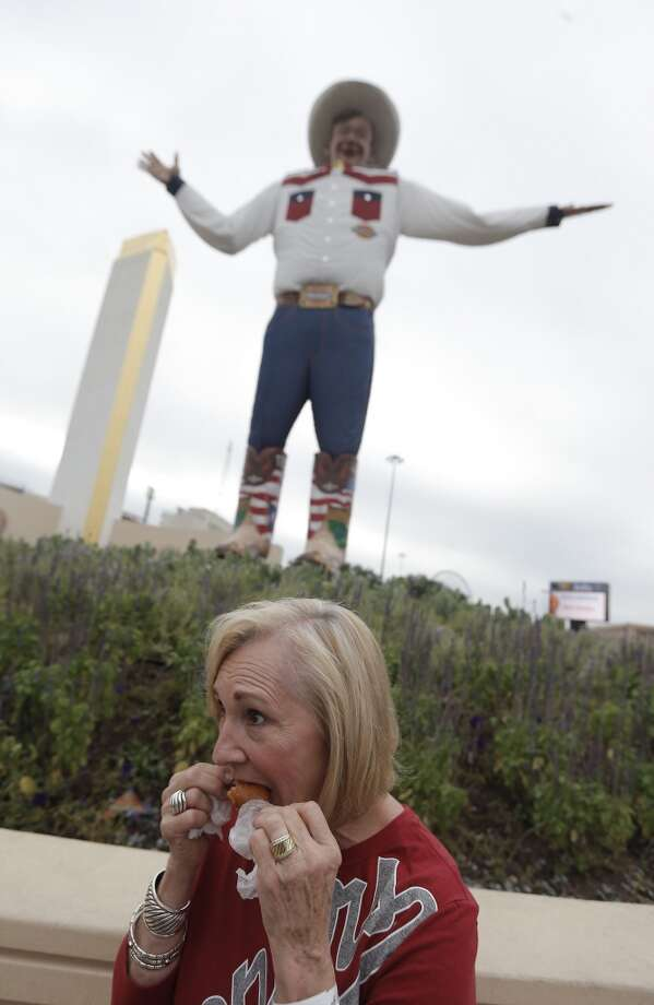 Linda Warren eats a corn dog in front of the Big Texas statue. Photo: Brandon Wade, Associated Press