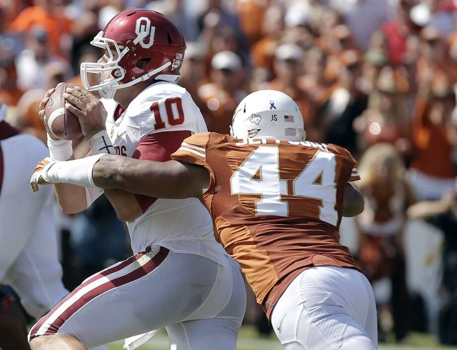Oklahoma quarterback Blake Bell (10) is sacked by Texas defensive end Jackson Jeffcoat (44) during the first half. Photo: Brandon Wade, Associated Press