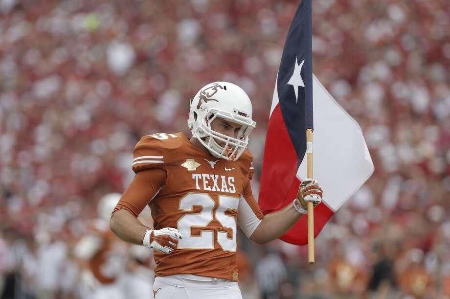 Texas wide receiver Michael Wheeler (25) carries the Texas state flag onto the field before the game. Photo: Brandon Wade, Associated Press