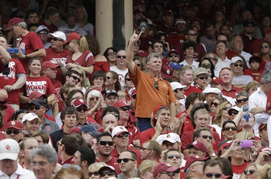 A lone Texas fang gives the Hook 'em Horns sign among Oklahoma fans during the first half. Photo: LM Otero, Associated Press