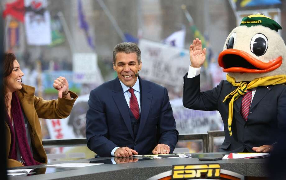 Hope Solo shares her thoughts as Lee Corso, right, puts on the Oregon Duck's mascot head as he choses the Ducks to win during a broadcast of ESPN's College Game Day in Red Square on the University of Washington campus. At center is broadcaster Chris Fowler. It was the first time the popular show has been broadcast from Seattle. Photographed on Saturday, October 12, 2013.  (Joshua Trujillo, seattlepi.com) Photo: JOSHUA TRUJILLO, SEATTLEPI.COM