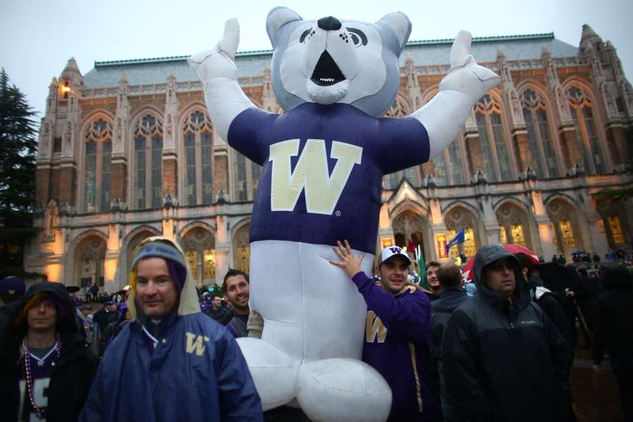 Fans carry an inflatable Husky during a broadcast of ESPN's College Game Day in Red Square on the University of Washington campus. It was the first time the popular show has been broadcast from Seattle. Photographed on Saturday, October 12, 2013.  (Joshua Trujillo, seattlepi.com) Photo: JOSHUA TRUJILLO, SEATTLEPI.COM