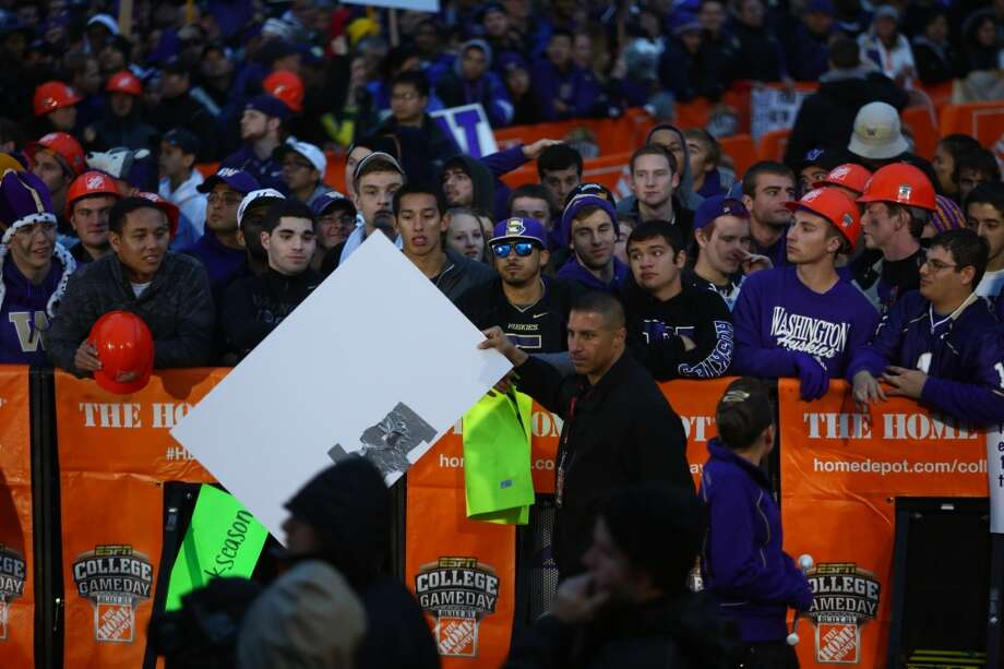 A sign is confiscated during a broadcast of ESPN's College Game Day in Red Square on the University of Washington campus. It was the first time the popular show has been broadcast from Seattle. Photographed on Saturday, October 12, 2013.  (Joshua Trujillo, seattlepi.com) Photo: SEATTLEPI.COM