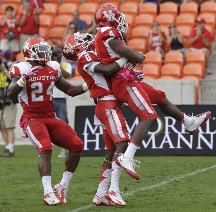 Cougars Kent Brooks, left, and Larry McDuffey, center, celebrate touchdown by teammate Daniel Spencer during the first quarter against the Memphis Tigers at BBVA Compass Stadium. Photo: Melissa Phillip, Houston Chronicle